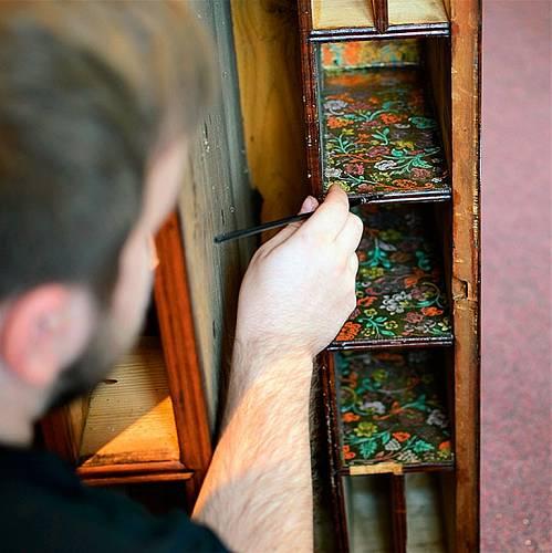 Student Marek pracuje na původním papírovém výlepu sekretáře z poloviny 18. století