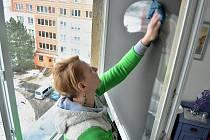39letá Michaela z úklidové firmy Sanace PO umývá okna v paneláku v mostecké ulici Maxima Gorkého, kde v sobotu v noci hořelo