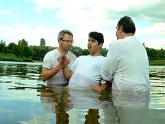 Pastor Róbert Liba (vlevo) a jeho zástupce Oldřich Gremlica křtí 14letého Tomáše v mosteckém jezeru Benedikt.