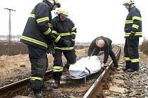 Hasiči odnášejí zabalené mrtvé tělo z kolejí, kde se nehoda stala.