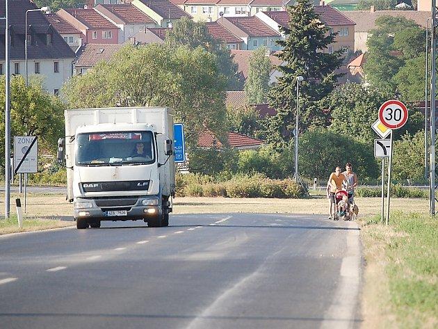 Tady je ještě město, ale cesta pro pěší ne. Miroslav Peška jde s rodinkou po silnici ze Vtelna do Mostu. Za ním jde jeho sestra. Autobus MHD tudy jezdí jen pozdě večer v pracovní dny a o víkendy jednou za hodinu. Chodci jakoby tu byli druhořadými.