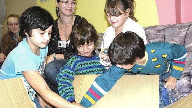 Děti z mosteckého azylového domu rozbalují dárky.