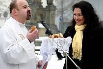 Farář Jiří Veith koštuje buchty od Jany Bobošíkové na mosteckém náměstí.