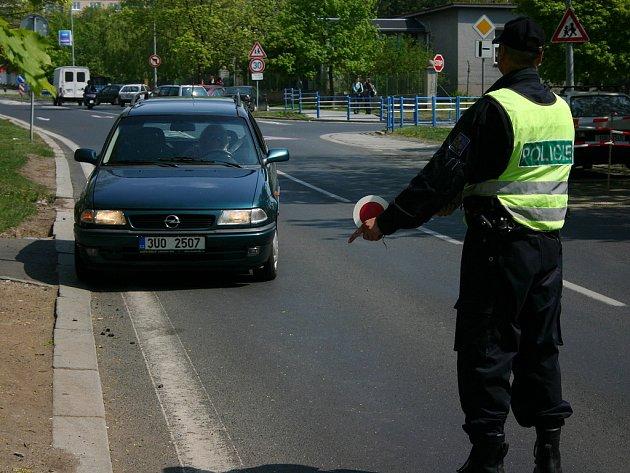 Policisté staví vozidlo při dopravně - bezpečnostní akci u 10 základní školy v Mostě.