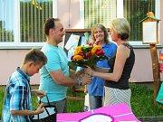 Tatínek dává paní učitelce velkou kytici.