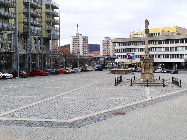 Liduprázdné náměstí v Mostě. Ve stejný čas se skupinky lidí procházely, postávaly či seděly v okolních ulicích.