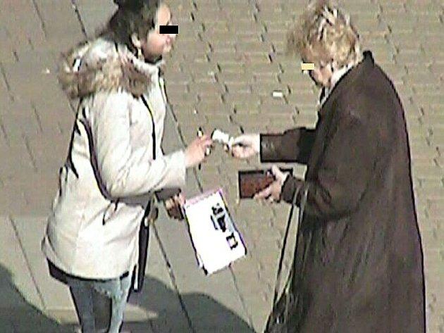 Seniorka předává podvodnici peníze. Ilustrační foto.