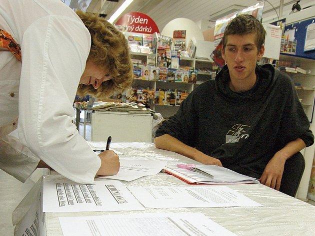 Žena podepisuje petici proti snížení nájmů v Chánově.