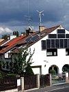 Dům je pokrytý solárními panely, na střeše je větrník.