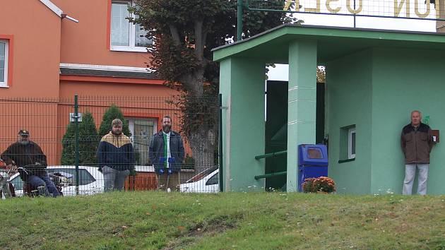 Fanoušci Baníku Osek za plotem sledují zápas.
