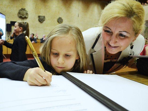 Osmiletá plavkyně Nathalie Anne Kučabová se podepisuje do pamětní knihy města Most při oceňování sportovců na radnici v prosinci 2014. Příští týden bude podobný ceremoniál v městském divadle.