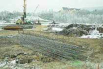 Těžká technika pomáhá stavbařům s přípravou území pro nový most. Auta se po něm dostanou do neosídlené části okresu, která se má začít rozvíjet.