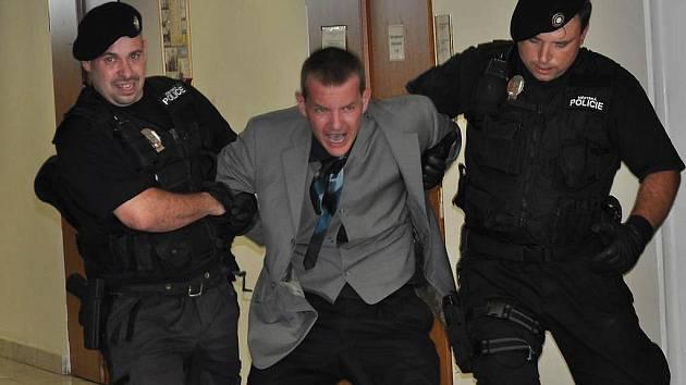 Strážníci vyvádějí agresora z budovy magistrátu.