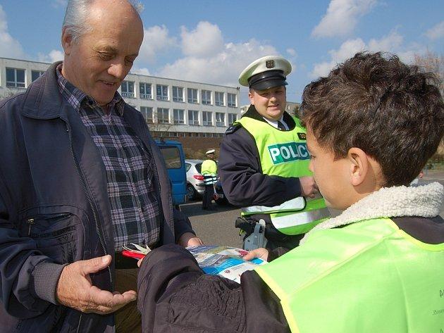 Školáci z páté třídy pomáhali policistům při dopravní akci v Obrnicích. Řidičům rozdávali za odměnu sluníčka a za trest mráčky.