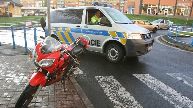 Policie objíždí odstavenou motorku po nehodě u 14. ZŠ v Mostě.