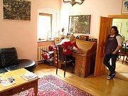 Obývací pokoj vedle jídelny. Véna klečí za pracovním stolem tatínka, stůl je po dědečkovi.