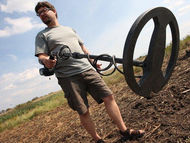 Jiří Šlajsna z Oblastního muzea v Chomutově předvádí práci s analogovým detektorem kovů na zkoumaném území.