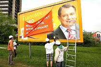 Aktivisté překrývají předvolební billboard s Jiřím Paroubkem.