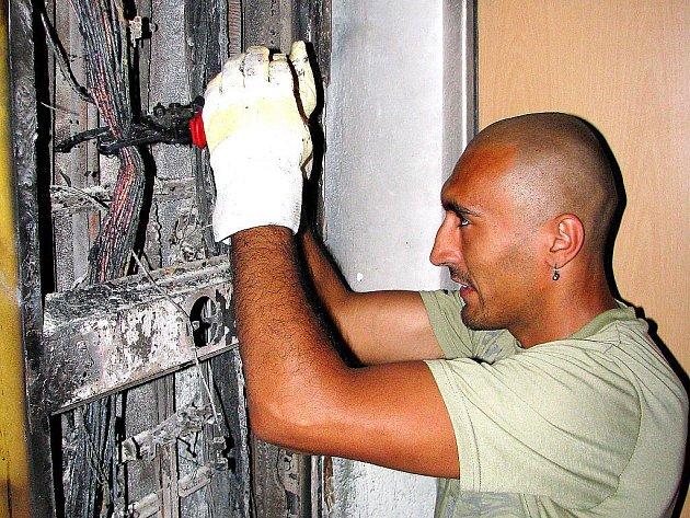 Dělník Petr Koločai odstraňuje shořelé kabely na chodbě věžáku u centra Mostu. Výškový obytný blok 383 hořel v pondělí. Oheň do bytů naštěstí nepronikl. Lidi ale málem udusil kouř.