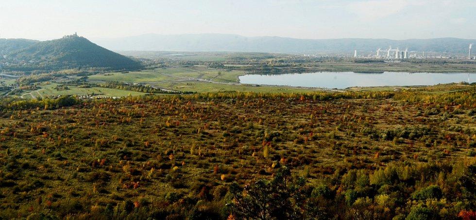 Pohled z vrchu Špičák na planinu, která se má proměnit na průmyslovou zónu. Nahoře vpravo je jezero Most s chemičkou v pozadí, nahoře vlevo budoucí rekreační oblast s vrchem Hněvín na obzoru.