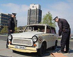 Strážníci prohlížejí poškozený reklamní trabant.