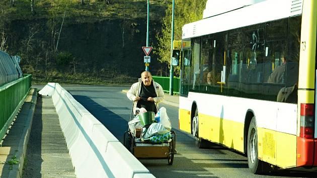 Muž tlačí kárku na rudolickém mostu, kde je novinkou betonová bariéra chránící prostor v oslabené části konstrukce. Po opravě, která se možná zvládne v roce 2016, se doprava opět vrátí do normálu a na most se vejde více aut.