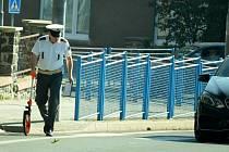 Policista vyšetřuje dopravní nehodu u gymnázia v Mostě.