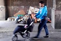Muž s kočárkem prochází kolem černé skládky ve Stovce. Mezi nábytkem jsou i běžné odpadky.