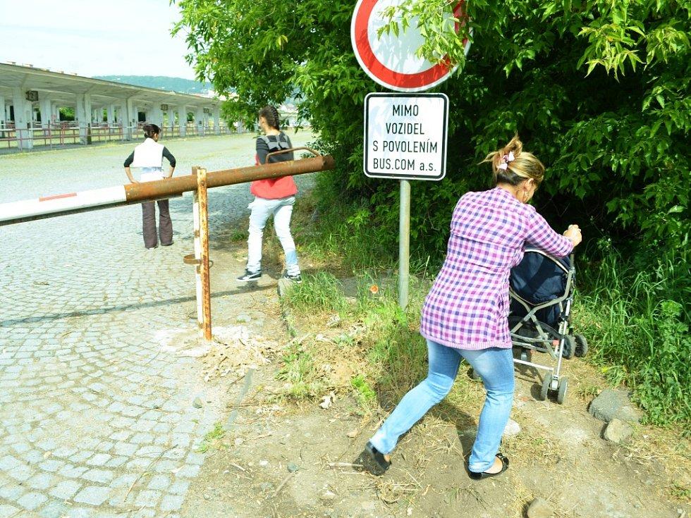 Žena se snaží dostat s kočárkem do Mostu poté, co vyjela z nového městského chodníku, který měl odstranit prostorovou odloučenost Chánova. Projekt podpořila EU v rámci boje se sociálním vyloučením. Mostu se nepodařilo opuštěné autobusové nádraží získat.