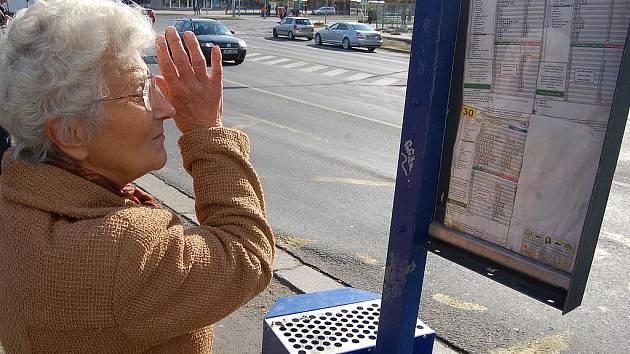 Žena si prohlíží jízdní řád na zastávce v centru Mostu. Modernější systém zatím nebude.