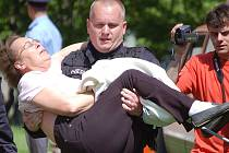 Ředitel mosteckých strážníků Bronislav Schwarz vynáší ženu z hořícího domu.