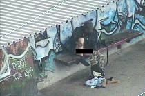 Jeden bezdomovec se svlékl na zastávce tramvaje u Stovky v Mostě a vykonal velkou potřebu. Zachytila ho městská kamera. To se stalo v roce 2010.