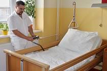 Vedoucí lékař Petr Myšák ukazuje, jak lůžka fungují. Polohovat se dá část pod hlavou i pod nohama.
