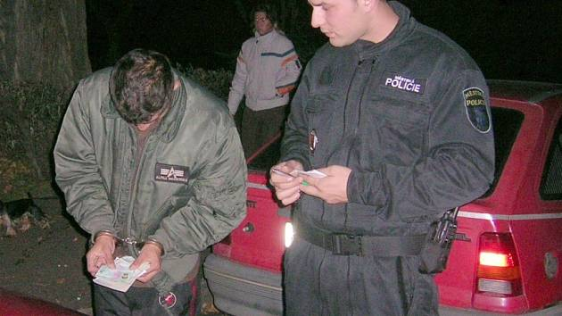Strážník zajišťuje řidiče, který má zákaz řízení.