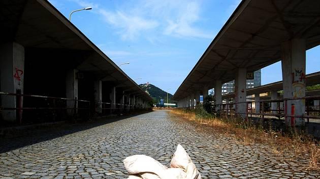 Polštář se válí na opuštěném autobusovém nádraží v Mostě. Vylidňuje se i město. Hovoří se o odlivu mozků, vzdělaní utíkají za lepším, byty často obsazují chudí z jiných regionů. Ujal se pojem sociální turistika.