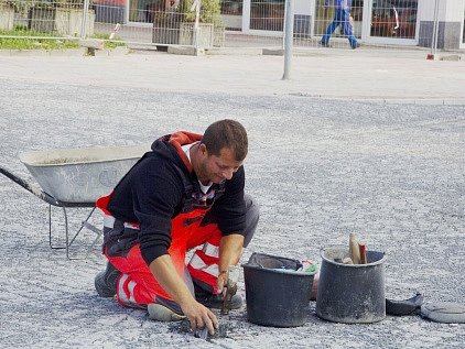 Dělník zatlouká poslední dlažební kostku v Mostecké ulici.