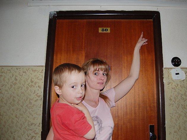 Obyvatelka Koldomu ukazuje na špatně usazené dveře. Mezi futry a dveřmi je několikacentimetrová mezera.