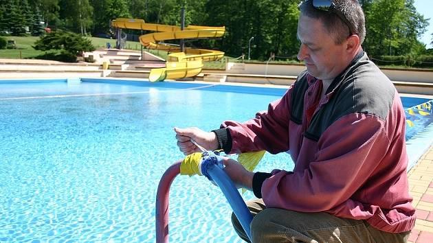 Jiří Vlček přivazuje zábrany kolem hlavního bazénu litvínovského koupaliště.