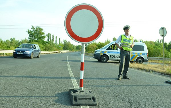 Policejní uzávěra na silnici uKomořan. Hlídky pouštějí zaměstnance okolních firem.