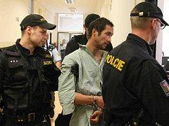 Policisté přivádějí k mosteckému soudu útočníka, kerý napadl policistu v Chánově