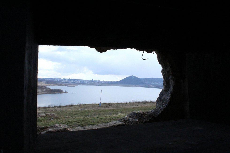 Pohled přes střílnu a díru v bunkru na jezero Most.