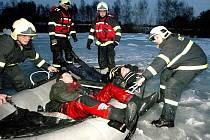 Hasiči zachraňují při cvičení tonoucí z ledové vody rybníku Bomba.