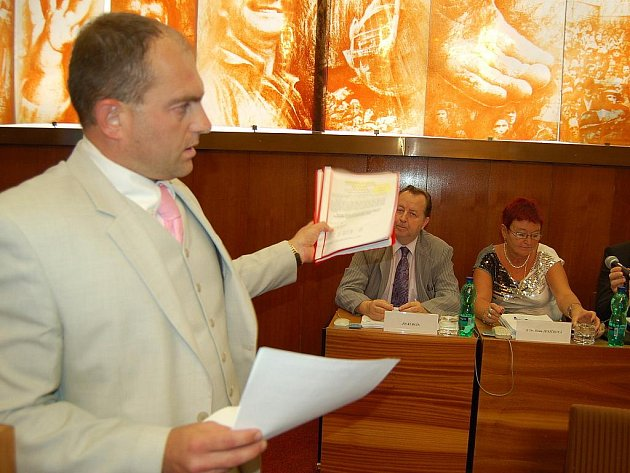 Zastupitel ČSSD Karel Novotný předává mosteckým radním petici proti snížení nájmu v Chánově o dvacet procent.