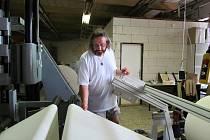 Marek Bajer u svého speciálně sestaveného stroje na výrobu materiálů pro zpevnění vazeb knih.