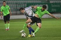Mostecký Rosendo (v zeleném) bojuje se soupeřem z Frýdku-Místku. V pozadí přihlíží Michal Nguyen, který mu přihrál na gól.