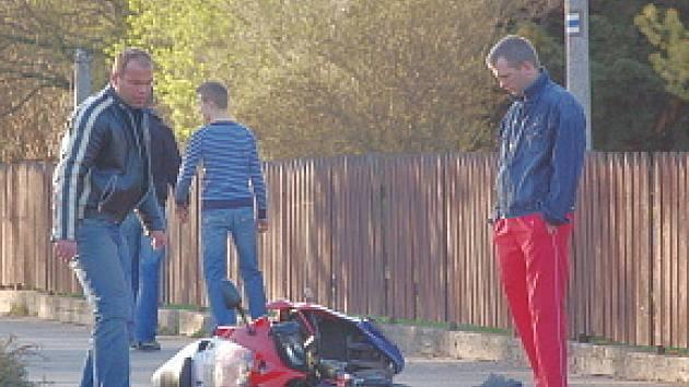 Řidič motorky (vlevo) chvíli po nehodě vstává a zjišťuje stav vozidla. Z nehody vyvázl jen s oděrkami.