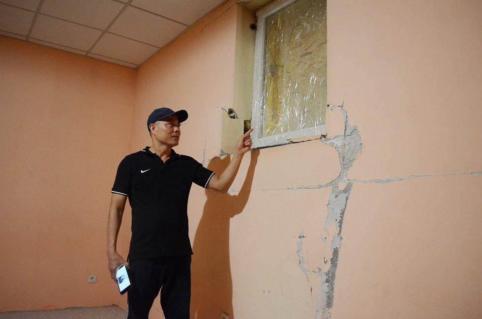 Nguyen Van Chi ukazuje poničenou stěnu a okno