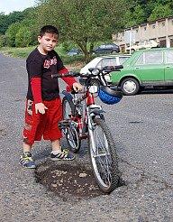 Josef Rouček ukazuje na díru v silnici. Nelíbí se mu tudy jezdit na kole. Rodiče se ho navíc bojí pouštět ven samotného.