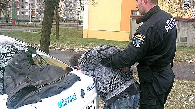 Mostecký strážník zadržuje muže, který napadal dalšího člověka.