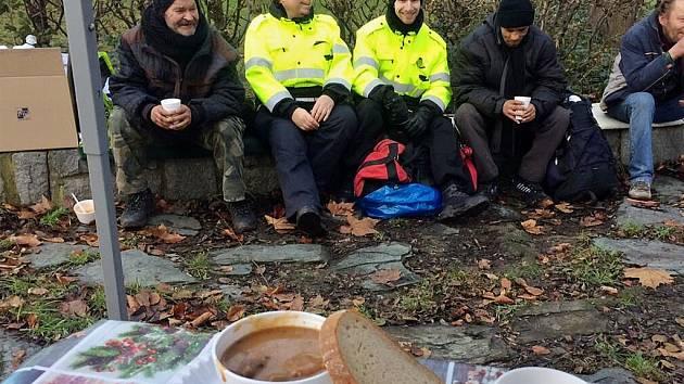 Zástupci mostecké městské policie, radnice a organizace K srdci klíč předali bezdomovcům v parku u sportovní haly zimní oblečení ze sbírky od veřejnosti.